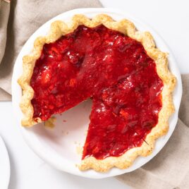 Top down view of red colored strawberry pie sitting on white countertop with extra strawberries on the side with taupe colored towel underneath