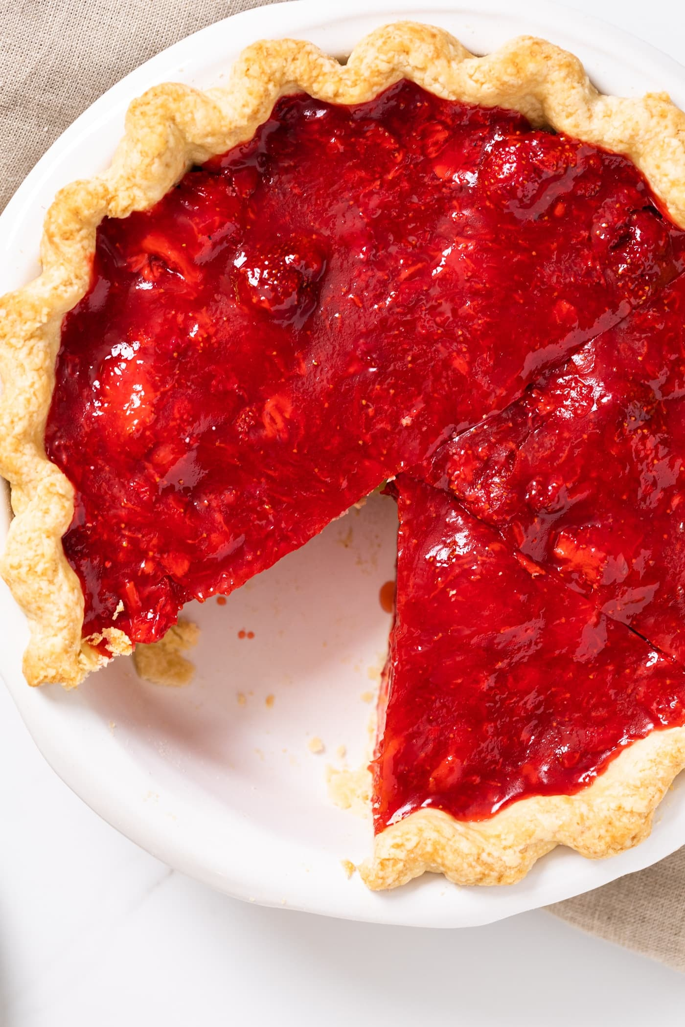 Top down view of strawberry pie with slice cut out sitting one white countertop