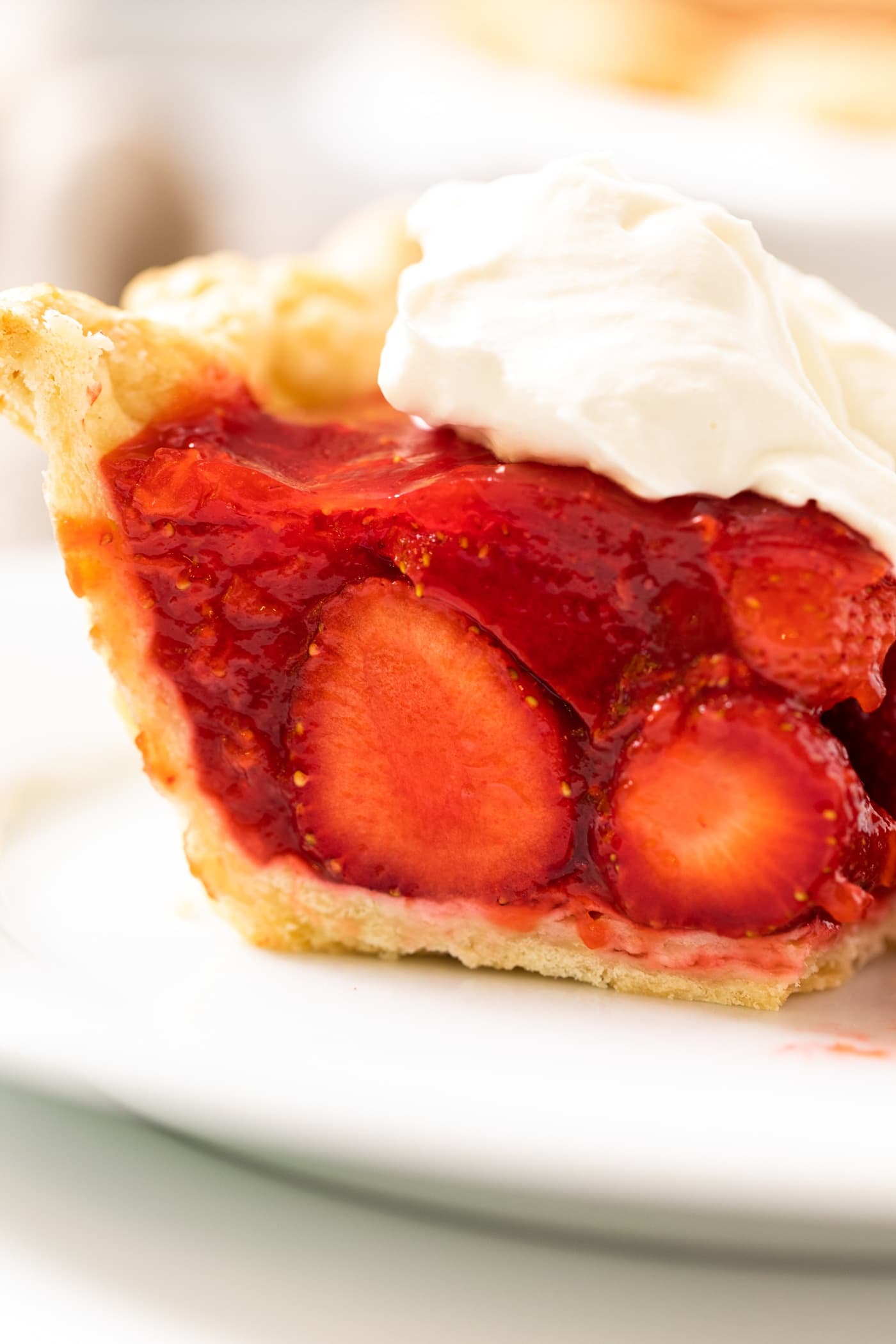 Side view of slice of red colored strawberry pie showing crust and cut slices of strawberries with piece of pie topped with whipped cream