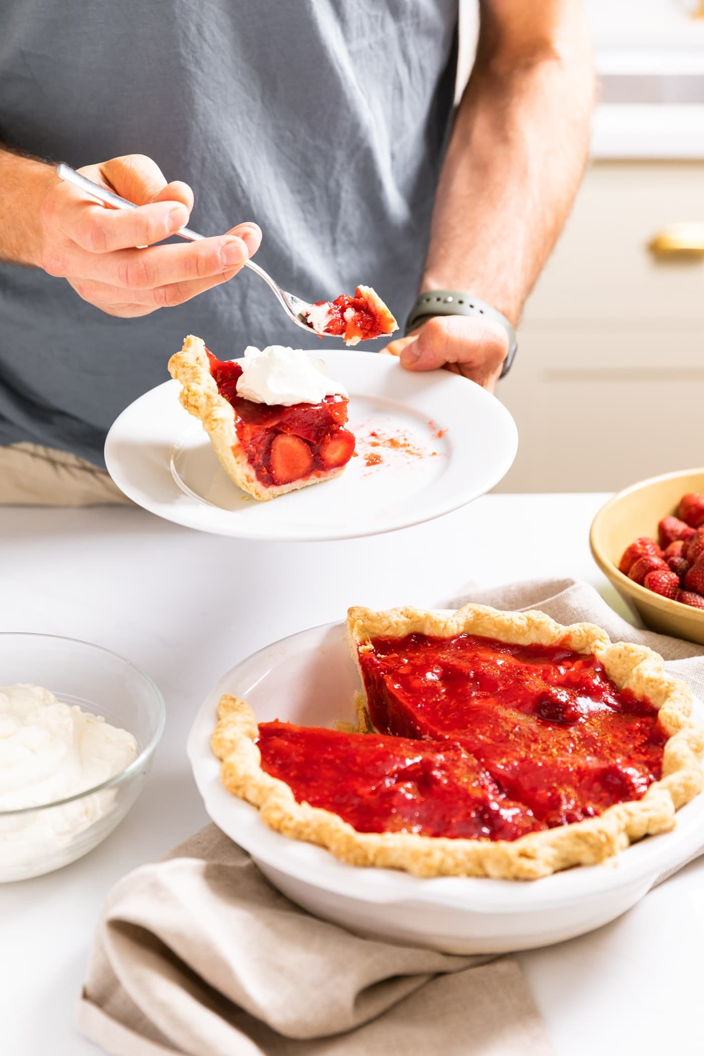 Two hands holding white plate with slice of strawberry pie sitting on it topped with whipped cream with rest of pie sitting below on white countertop