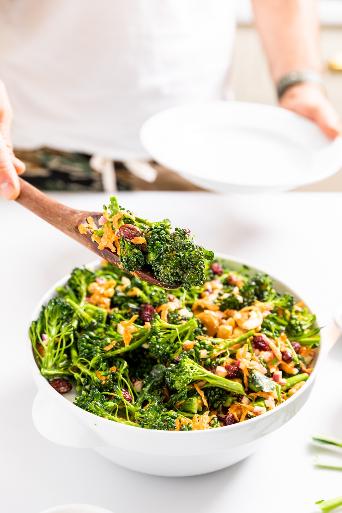 White bowl filled with broccoli florets topped with sauce and cashews and dried cranberries with hand holding wooden serving spoon