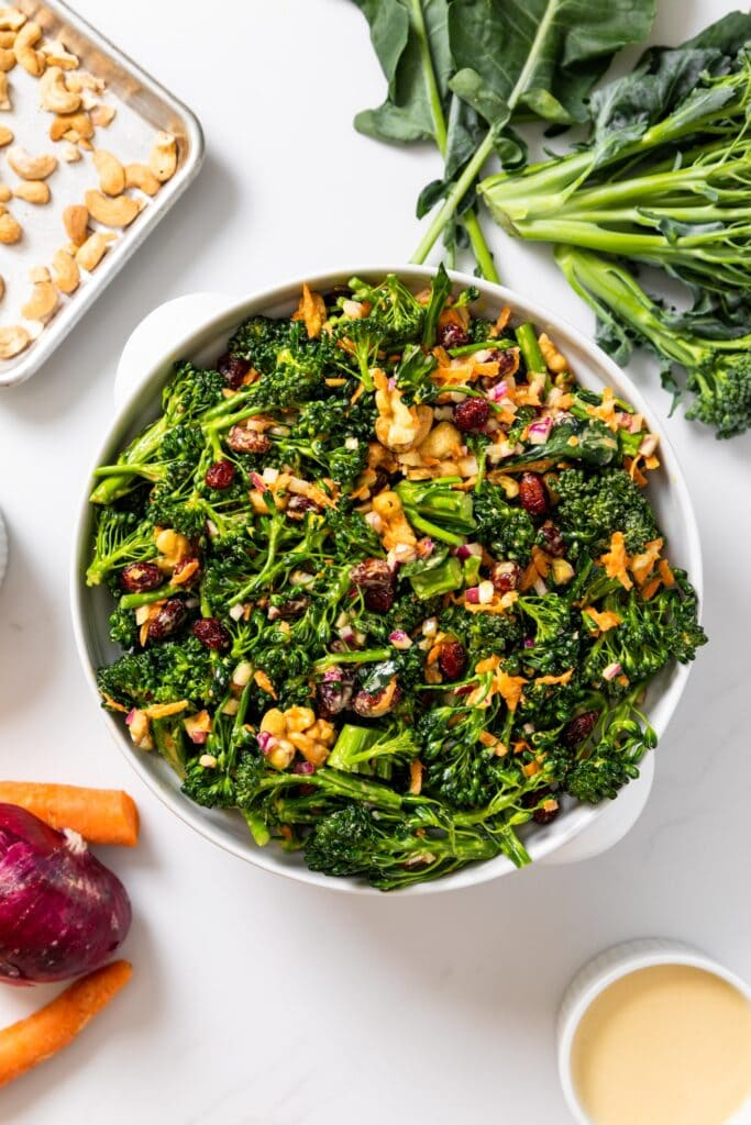 Top down view of white bowl holding broccoli florets topped with cashews with extra vegetables sitting around along with peach colored dressing