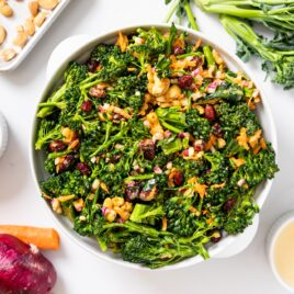 Top down view of white bowl filled with florets of broccoli tossed in dressing with dried cranberries and cashews on top with other ingredients sitting around on white countertop
