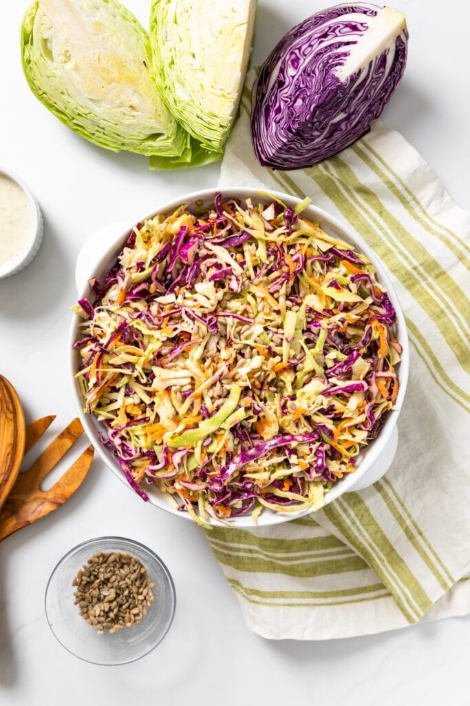Top down view of white bowl sitting on white countertop filled with brightly colored coleslaw in both green and purple with extra cabbage around