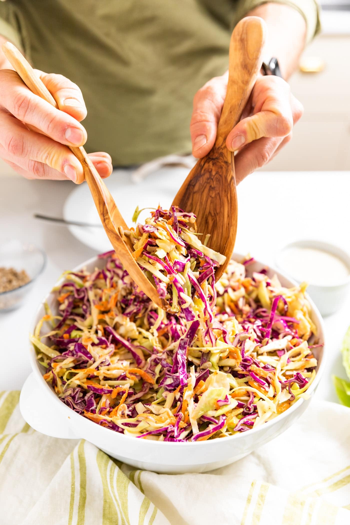 Two hands holding wooden tongs picking up red and green colored coleslaw