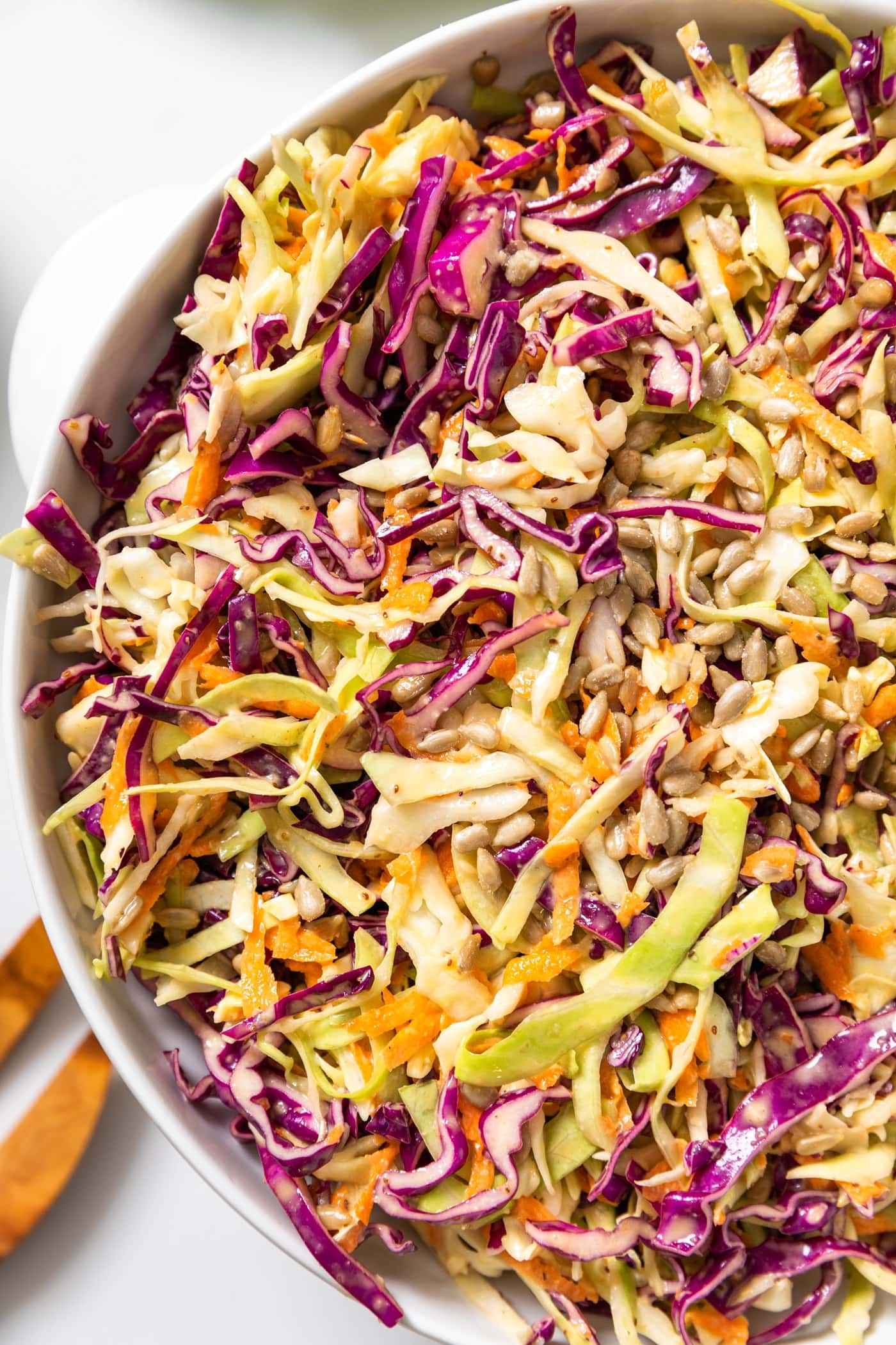 Top down view of white bowl with green and purple cabbage mixed with carrots sitting on white countertop
