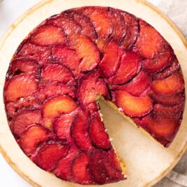 Top down view of plums laid out in an overlapping pattern on the top of a cake sitting on a cake stand with a towel underneath