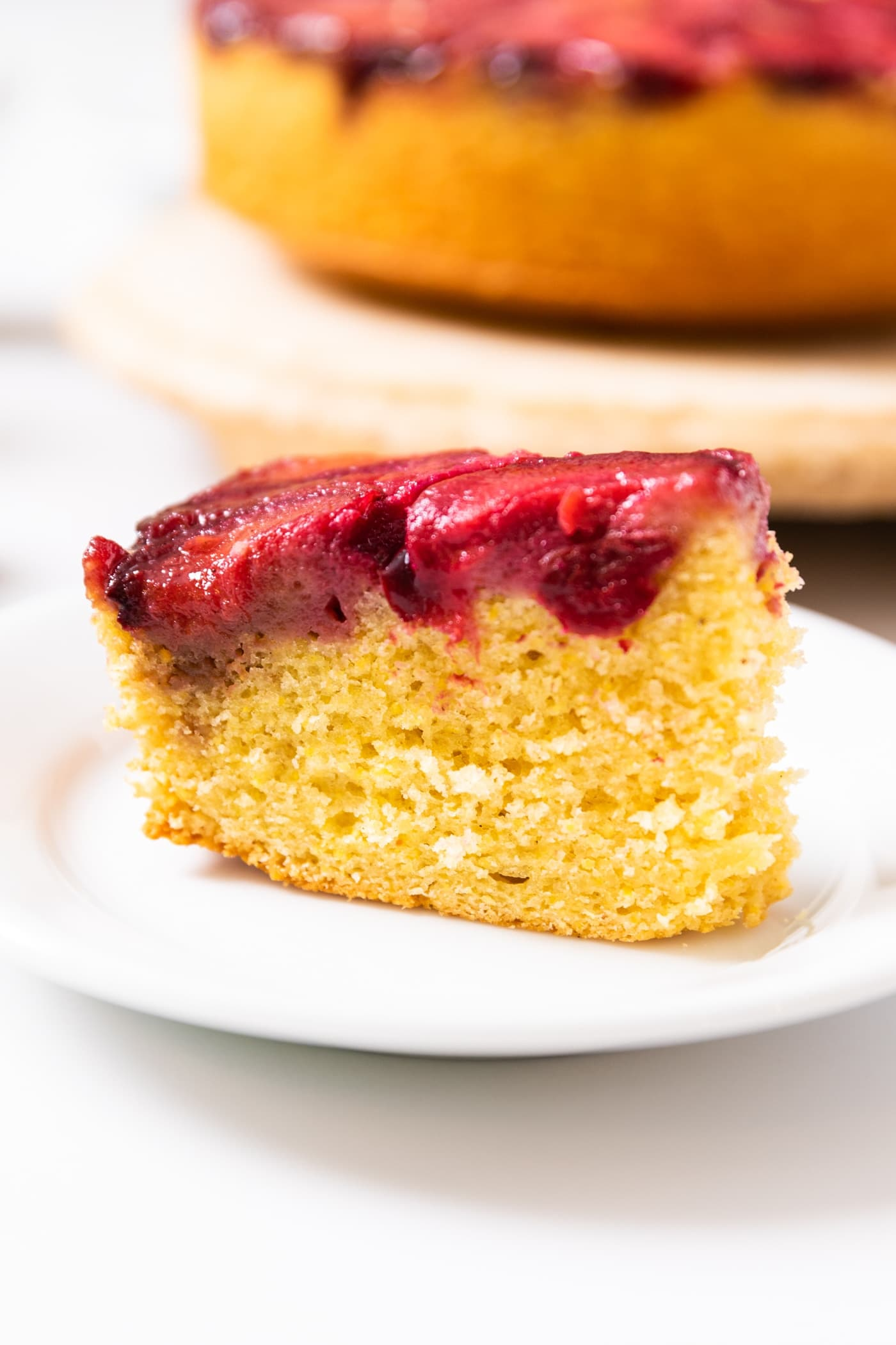 Side view of yellow colored cornmeal cake with a plum layer topping sitting on white plate with rest of cake in background