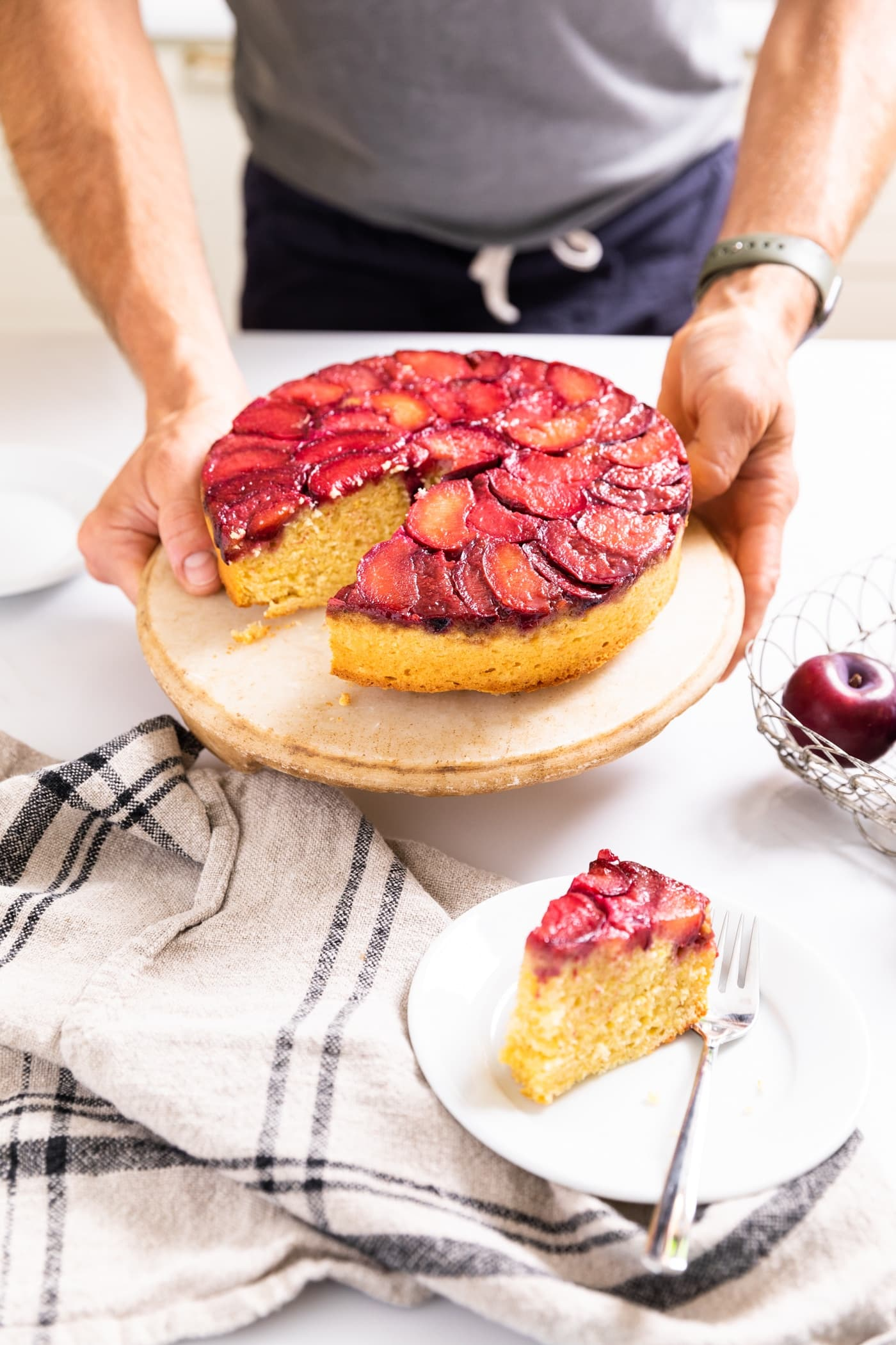 Two hands holding cake plate with cornmeal cake topped with slices of plums with slice cut out and sitting on white plate in front