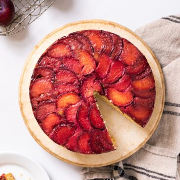 Top down view of bright red colored plum cake sitting on cake platter on white countertop with extra piece of cake and plums
