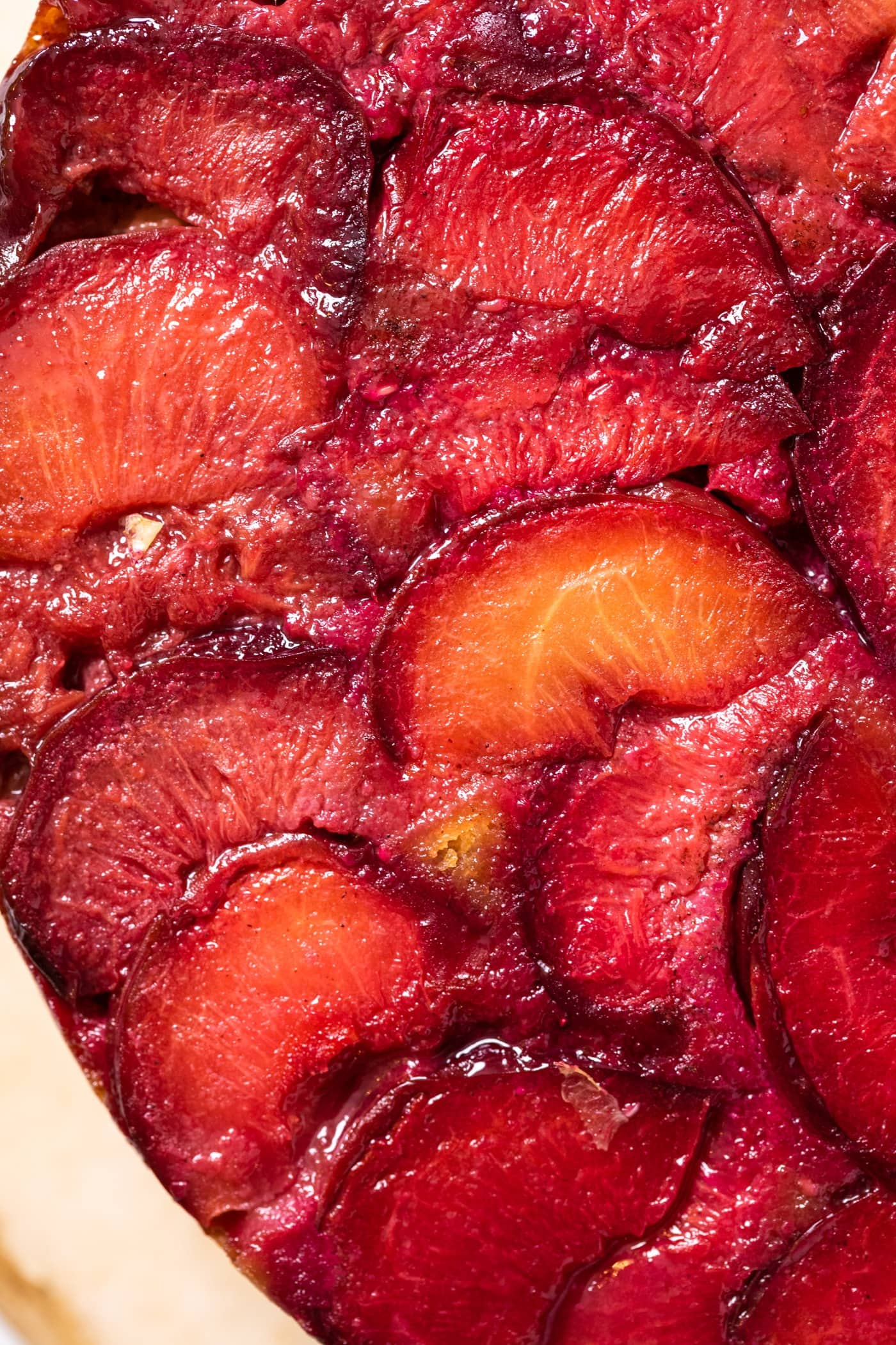 Top down close up view of slices of baking plum sitting on top of cornmeal cake with bright reds and light yellows