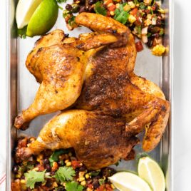 Top down view of orange colored grilled chicken sitting on steel container with limes and salsa around