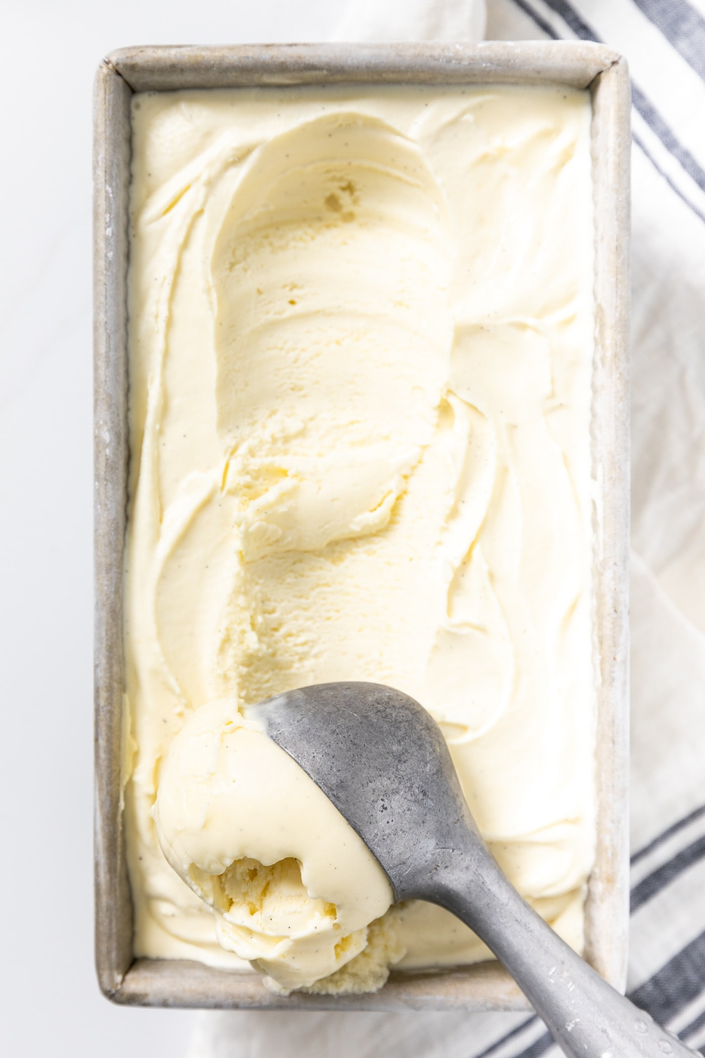 Close up view of ice cream scoop scooping vanilla ice cream from silver container in which it was frozen