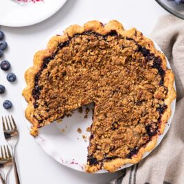 Top down view of circular blueberry pie sitting on white countertop with slice taken out and sitting on white plate with extra bowl of blueberries