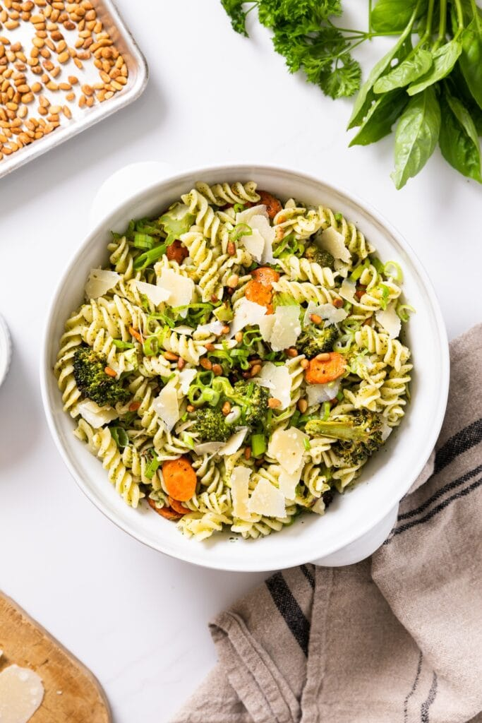 Top down view of white bowl filled with cooked pasta along with pieces of carrot and broccoli with extra herbs and pine nuts around