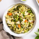 Top down view of white bowl filled with cooked pasta along with pieces of carrot and broccoli sitting on white countertop with towel underneath
