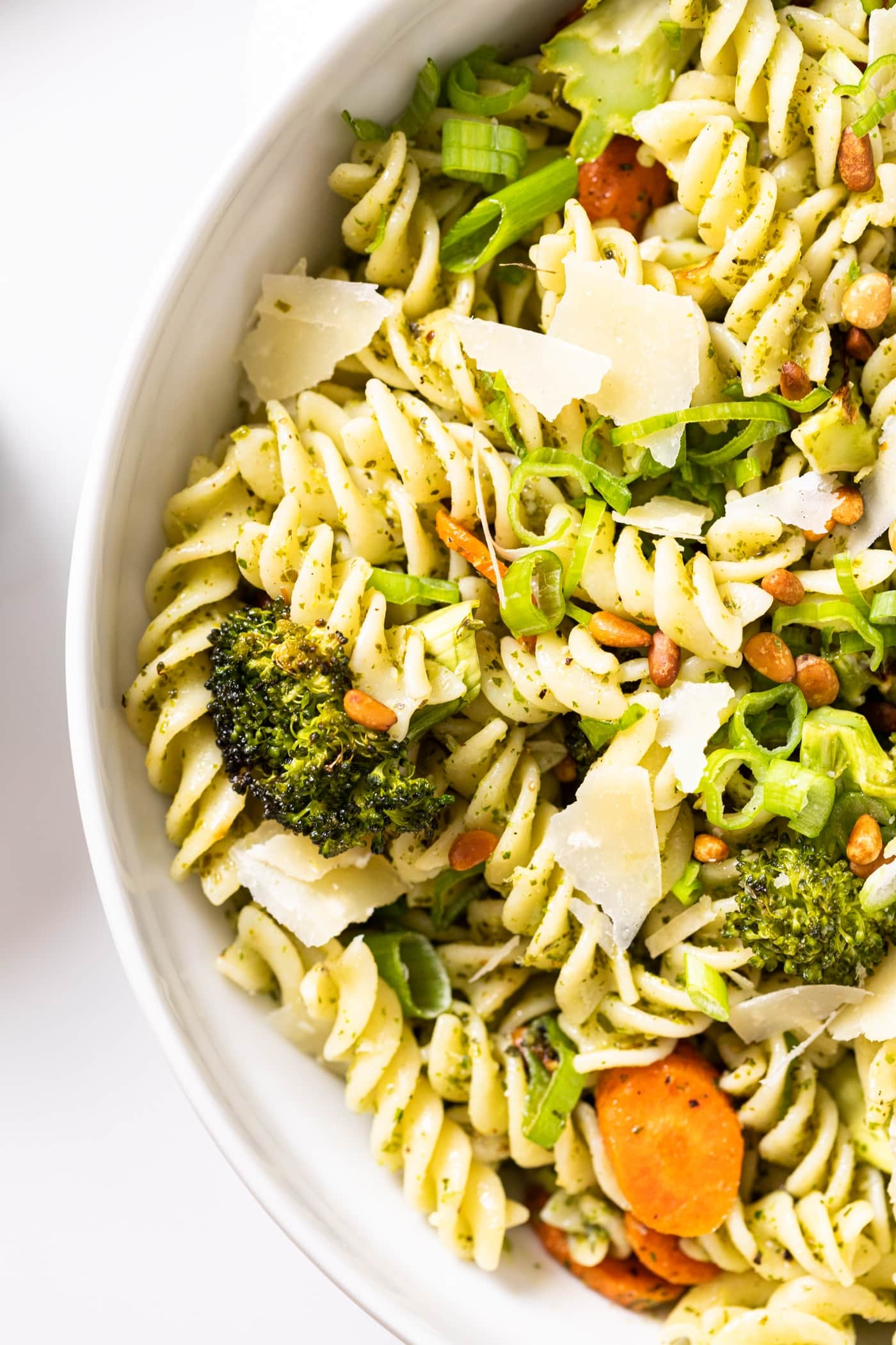 White bowl filled with pasta and carrots and broccoli and topped with Parmesan cheese and pine nuts