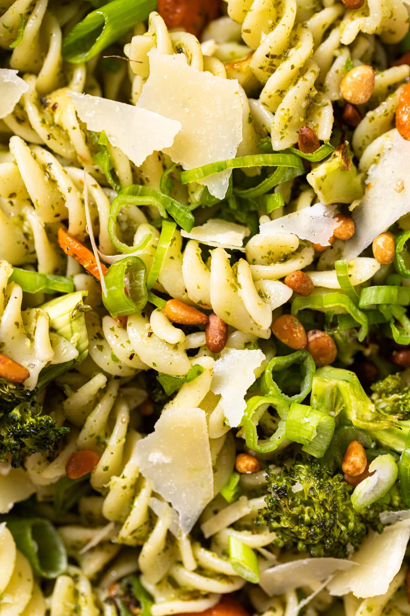 Close up view of cooked yellow pasta nestled with pieces of Parmesan cheese and broccoli and pine nuts