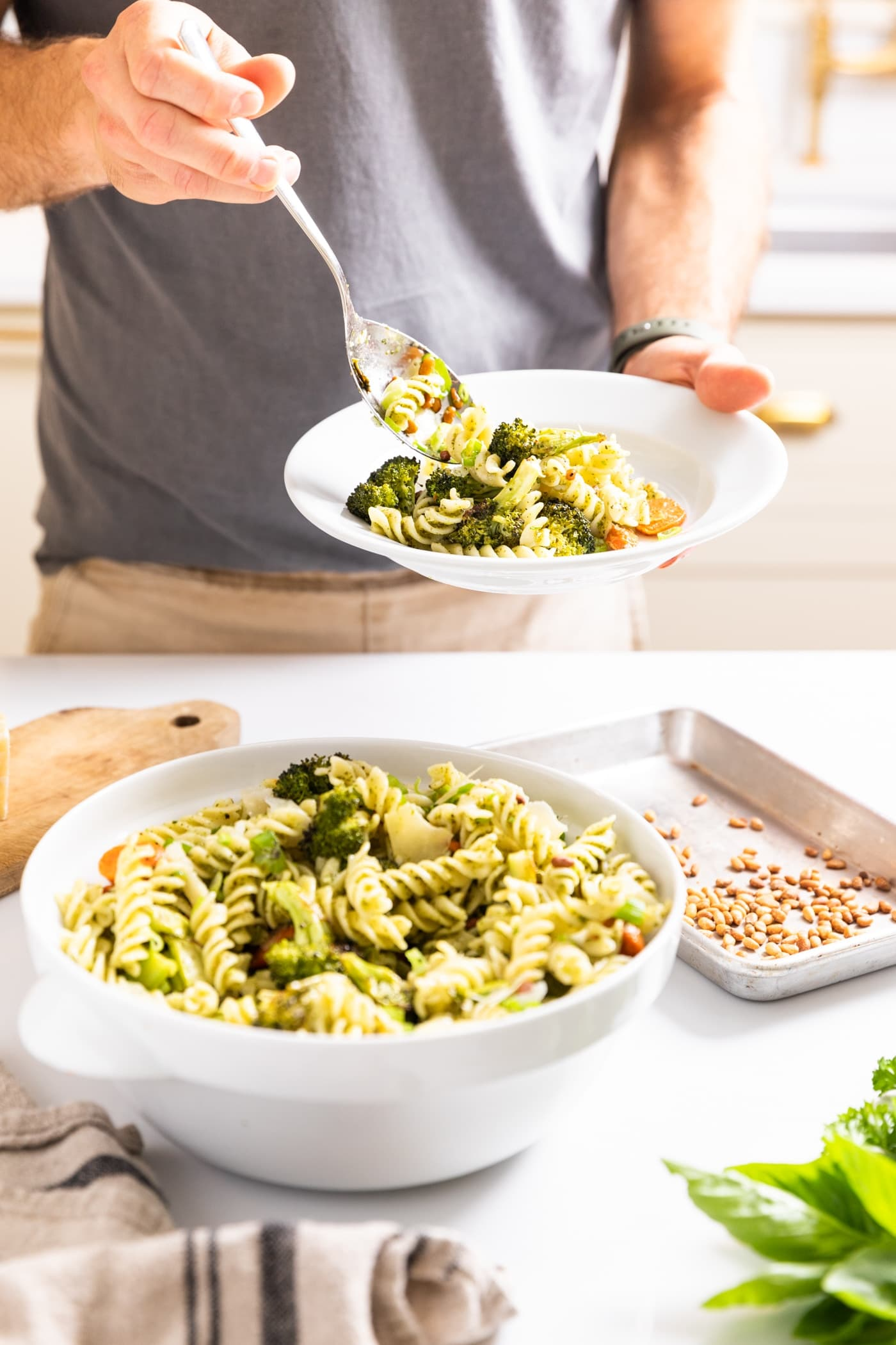 Hand holding white plate and scooping pasta salad onto plate from white bowl all on white countertop with tan cabinets in background