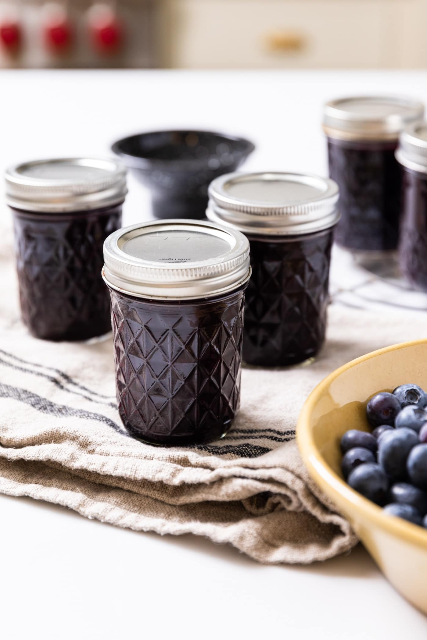 Glass jars with lids and rings on holding dark colored blueberry jam inside sitting on white countertop with bowl of blueberries in front