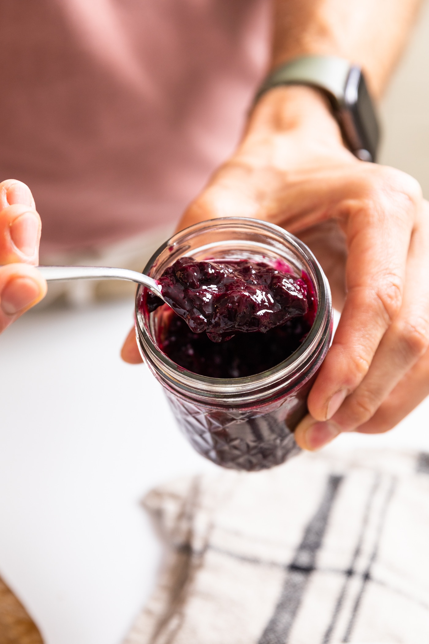 Hand holding glass jar filled with dark purple blueberry jam with other hand holding spoon scooping out some of the jam