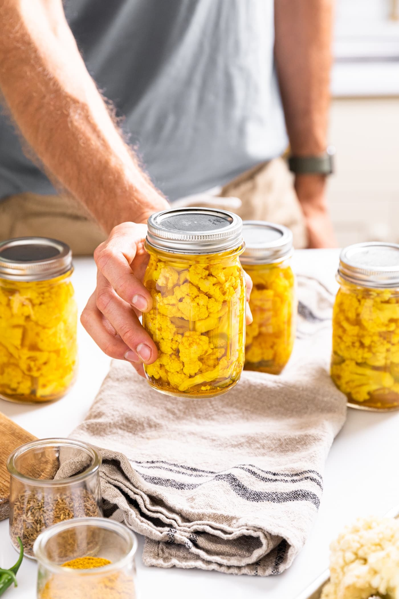 Hand holding glass jar filled with yellow pickled cauliflower with other filled jars in background all one white countertop with spices around