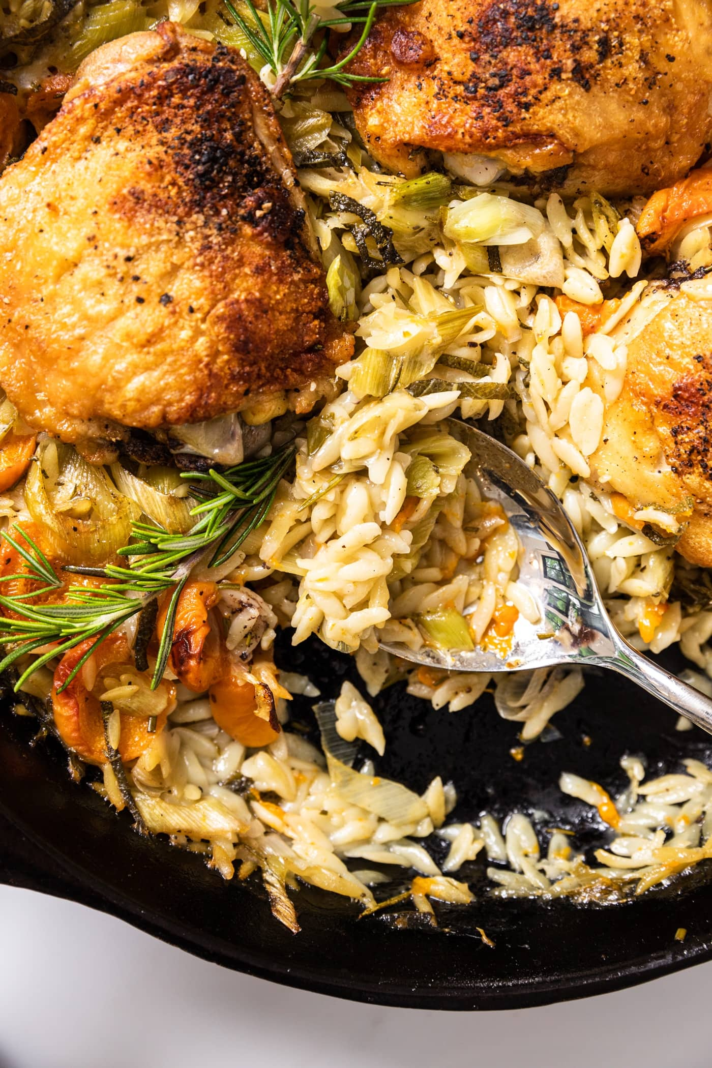 Top down view of spoon scooping out orzo from black skillet also filled with cooked chicken thighs