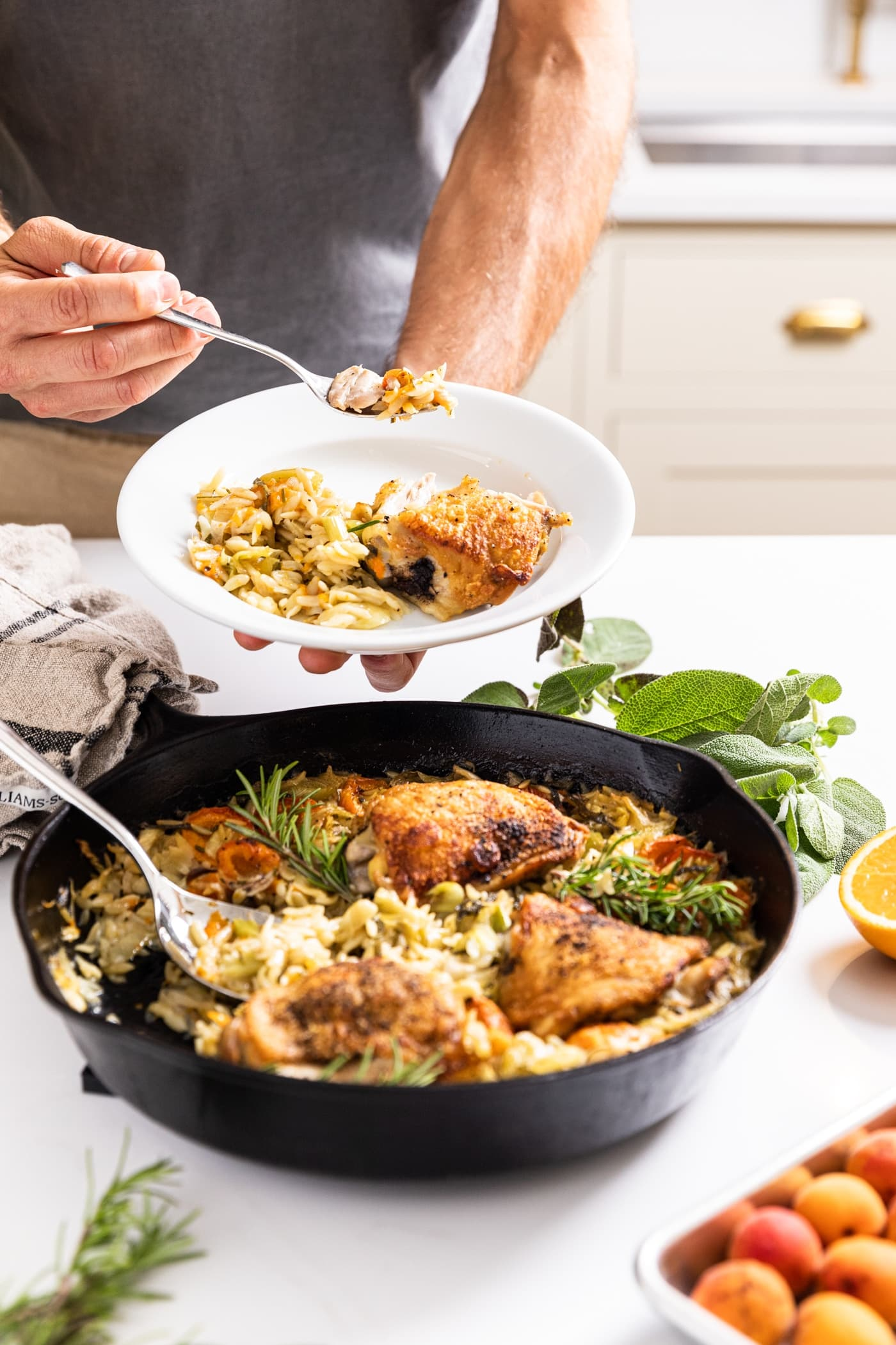Two hands holding white plate with fork holding piece of chicken after being scooped out of skillet underneath