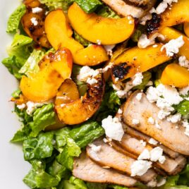 Top down view of white platter filled with slices of pork and nectarines topped with green dressing and pieces of white goat cheese