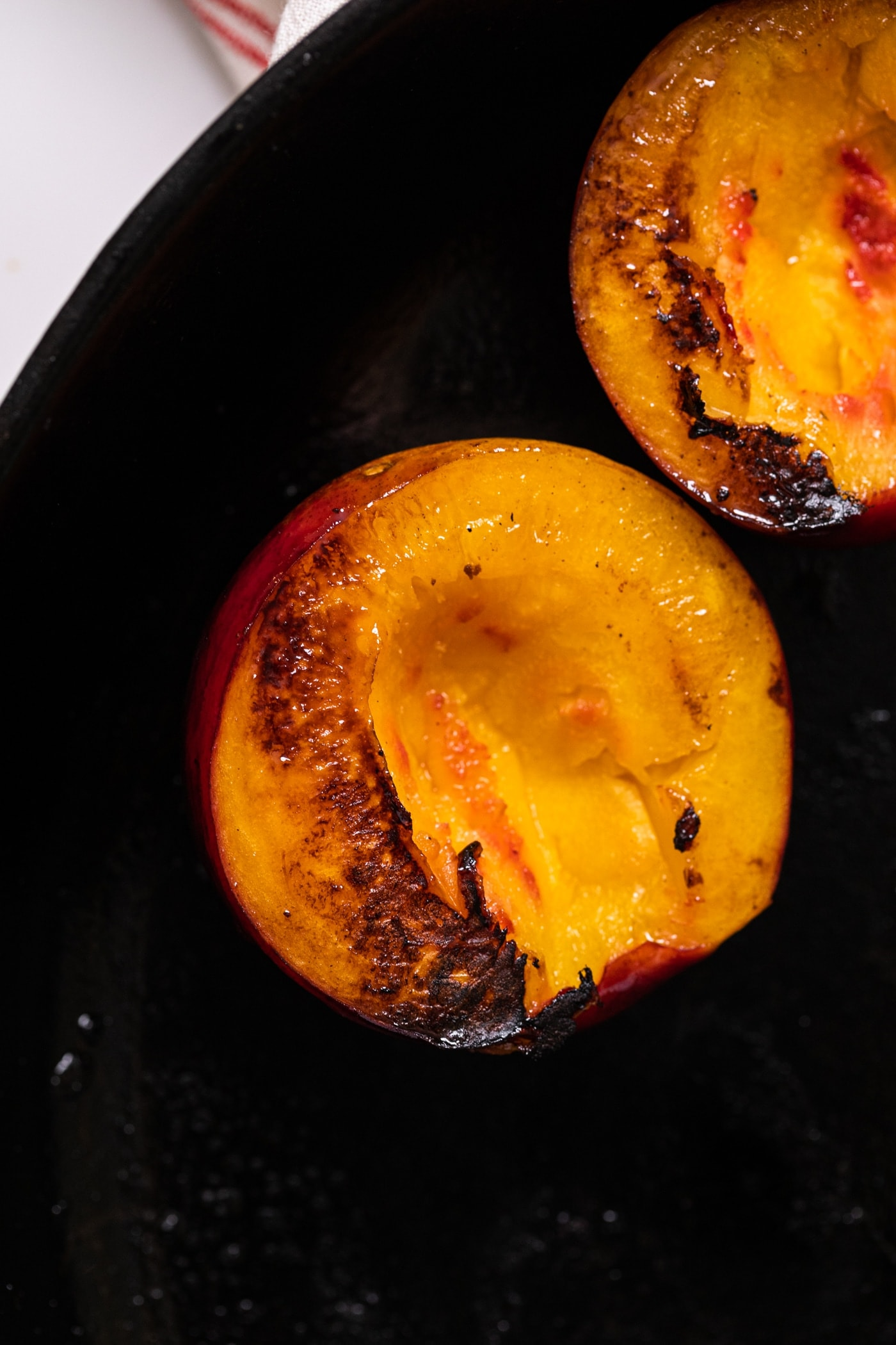 Top down view of grilled nectarine sitting in black cast iron skillet