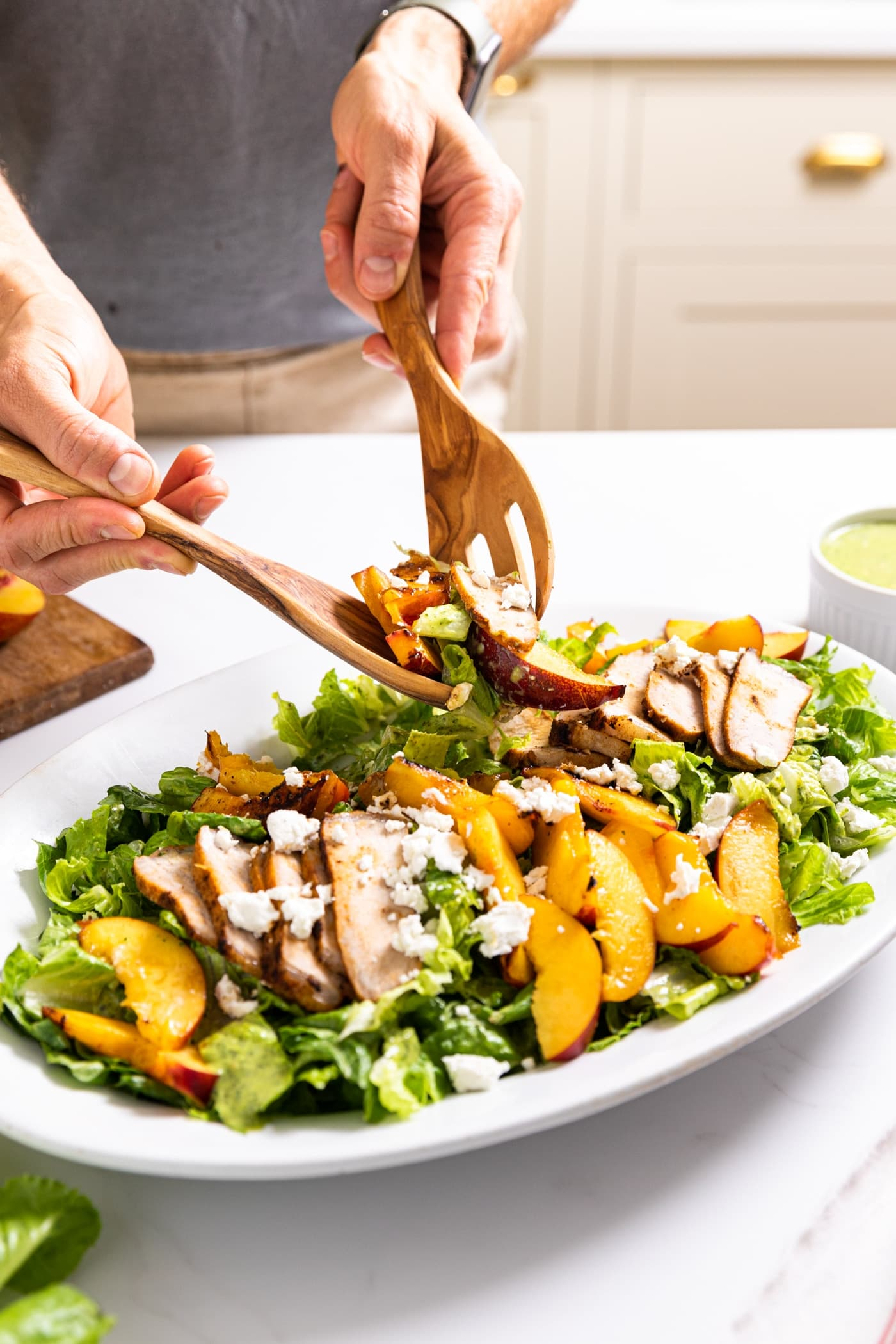 Two hands holding wooden tongs scooping up serving of salad from white platter filled with slices of nectarine and pork