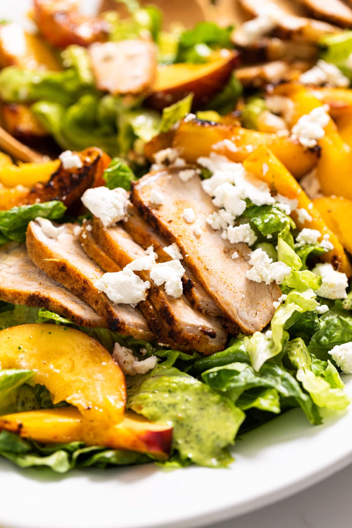 Close up view of white plate filled with lettuce topped with slices of pork and nectarines with goat cheese on top