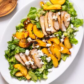 Top down view of white platter filled with lettuce and slices of nectarines and pork topped with goat cheese all on white countertop with components of salad all around