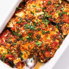 Top down view of white casserole dish filled with red colored eggplant parmesan with cheese and green herbs all over the top sitting on white countertop