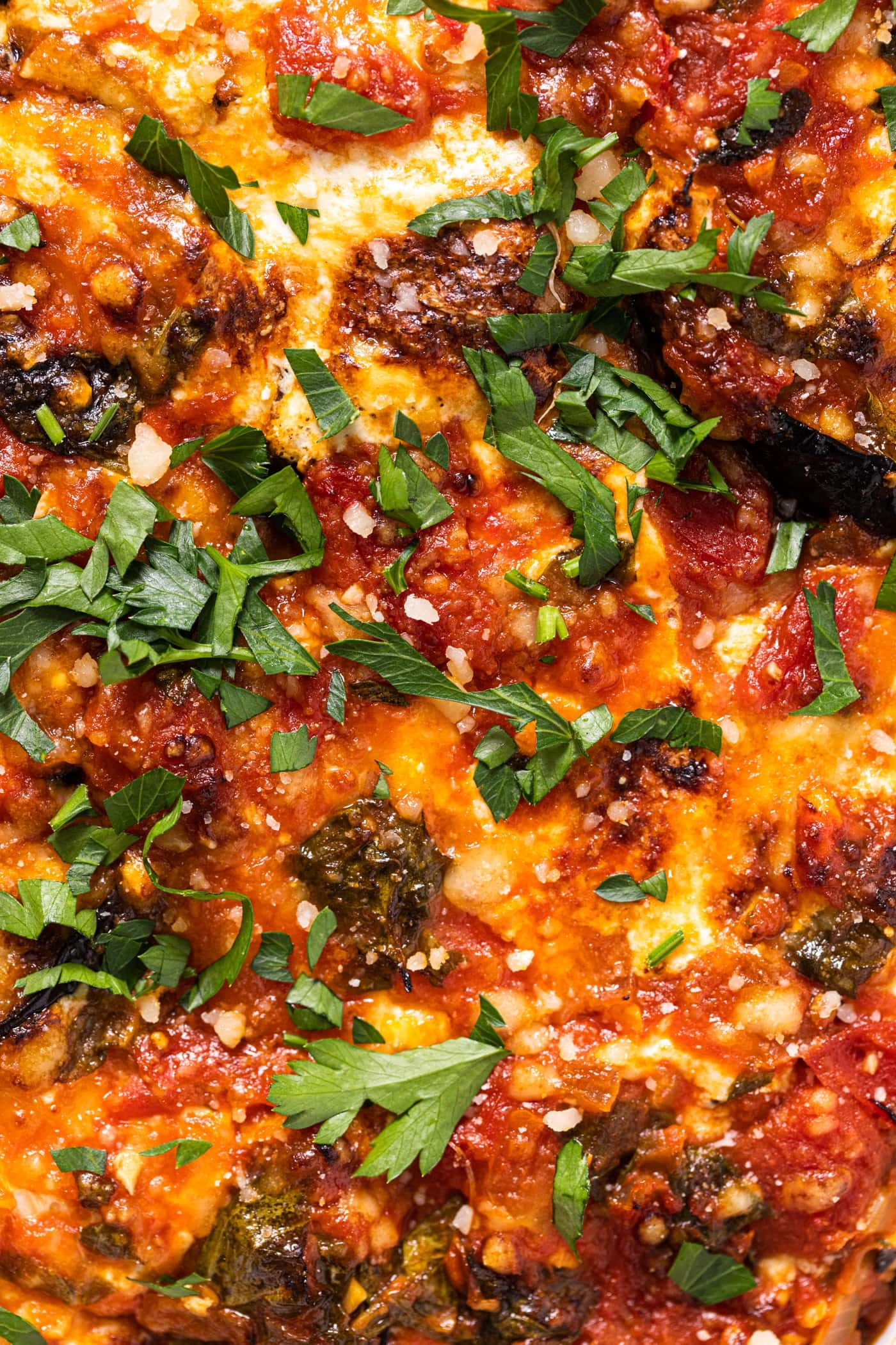 Close up view of the top layer of an eggplant lasagna recipe with bubbles of browned cheese and a fresh sprinkling of green herbs with bits of eggplant showing through the cheese