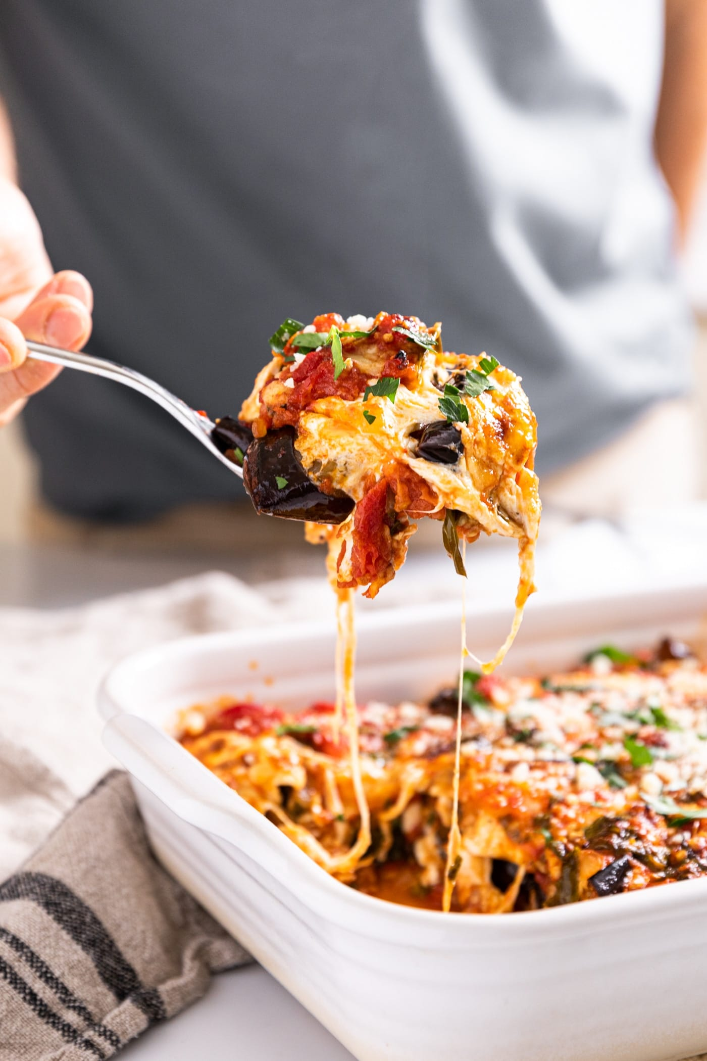 Hand holding scoop of eggplant parmesan from white baking dish after freshly being taken from the oven with strings of cheese still attached to rest of dish below