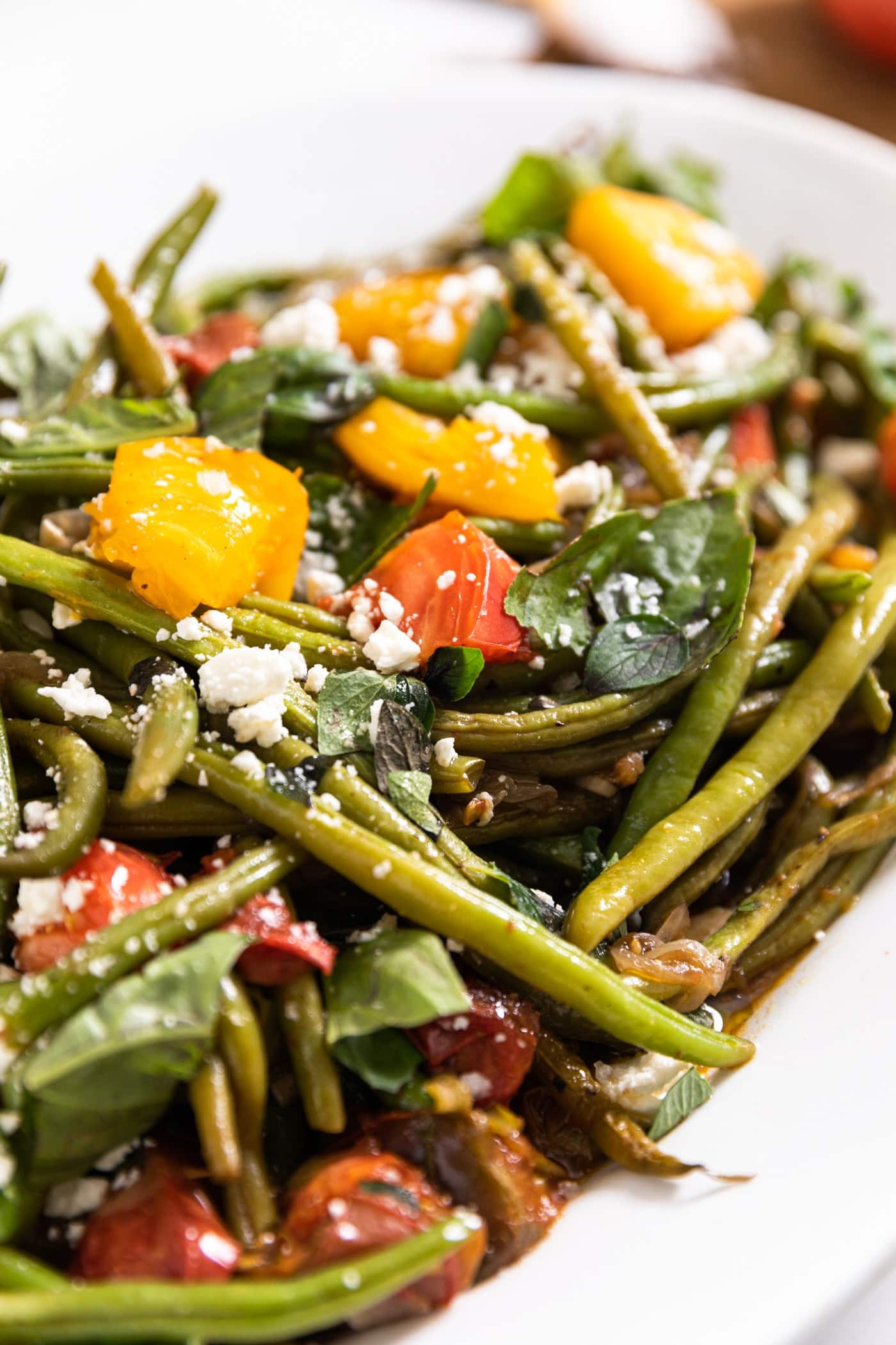 White platter filled with green beans and tomatoes and fresh herbs with feta cheese all over the top