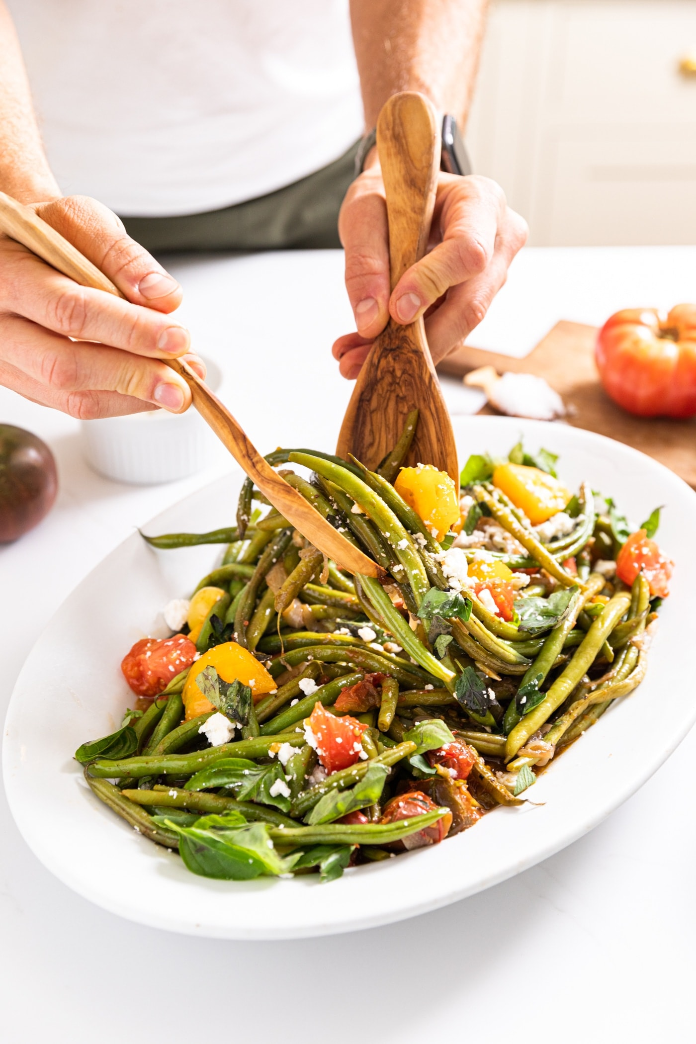 Two hands holding salad tongs pulling up serving of green beans and tomatoes from white platter sitting on white countertop with bright red tomato in background
