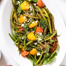 Top down view of white platter filled with green beans and roasted tomatoes sitting on white countertop