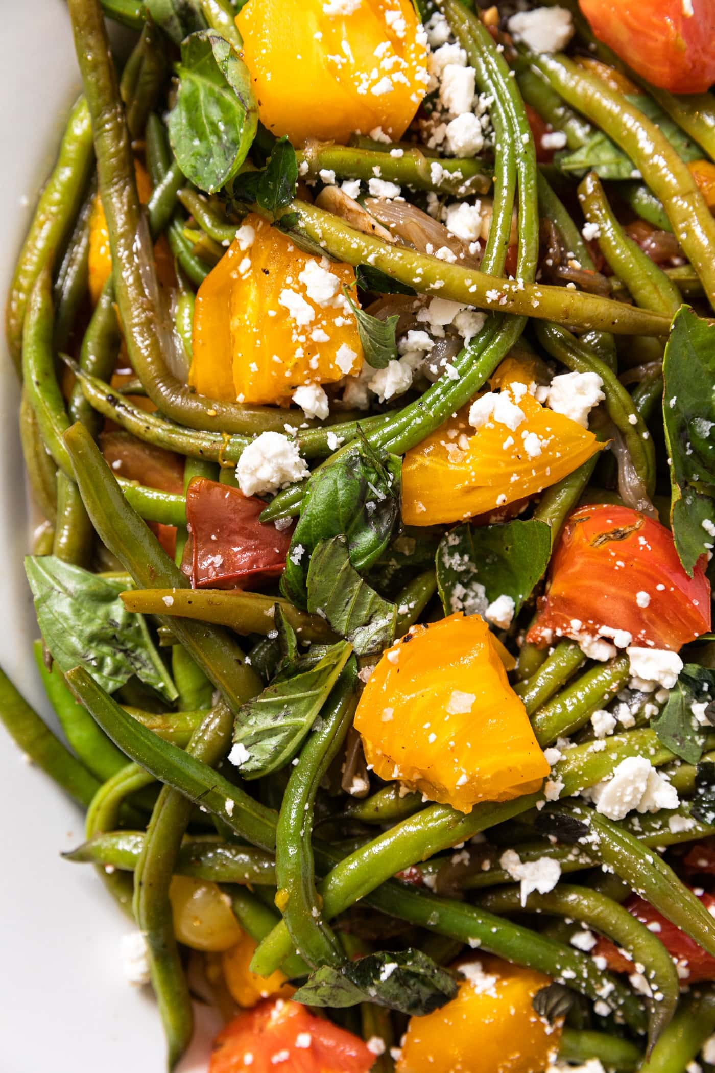 Top down view of white platter filled with green beans and topped with yellow and red tomatoes and topped with a sprinkling of feta cheese