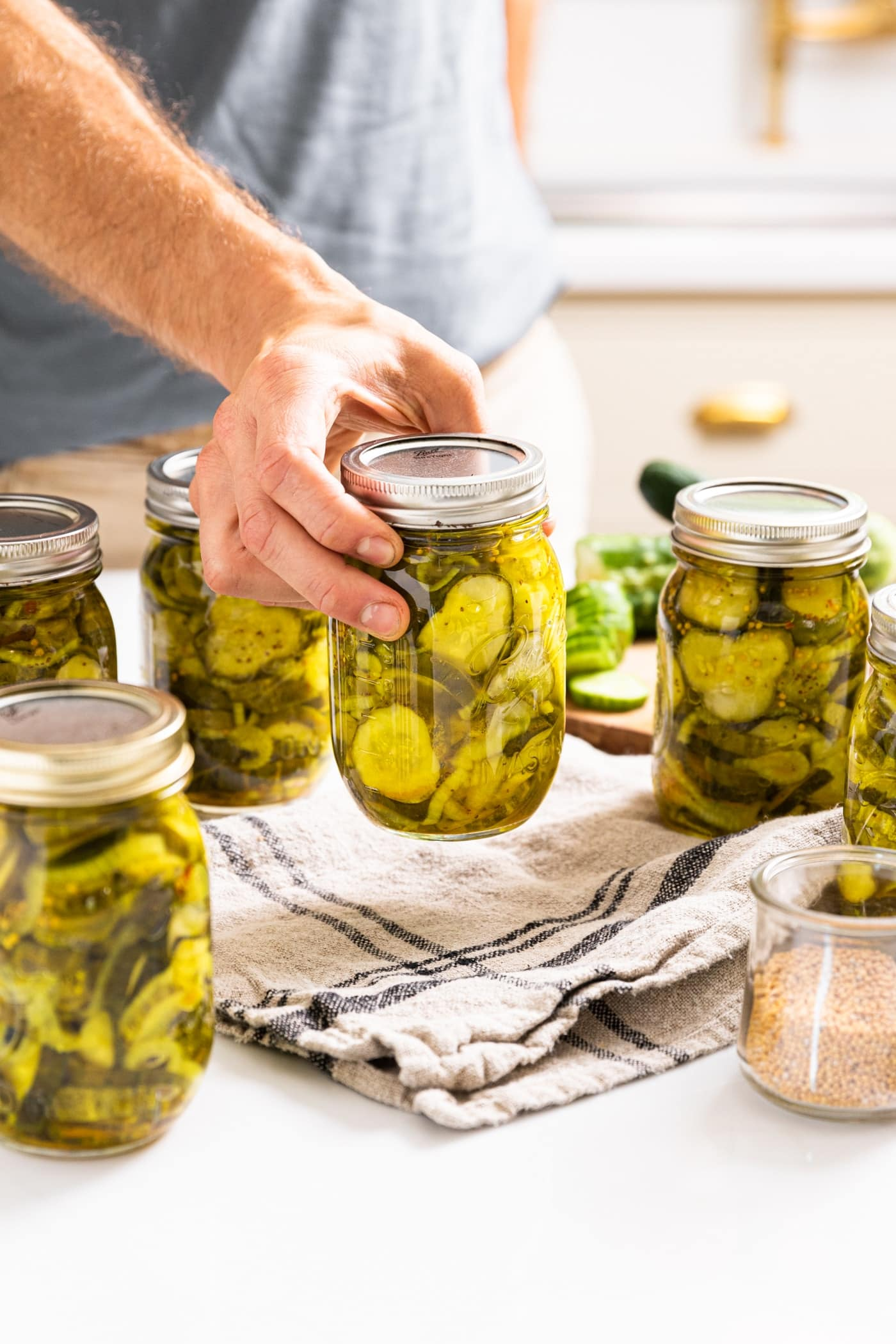 Hand holding glass jar filled with bread and butter pickles in the action of setting jar down on cloth with other glass jars all around