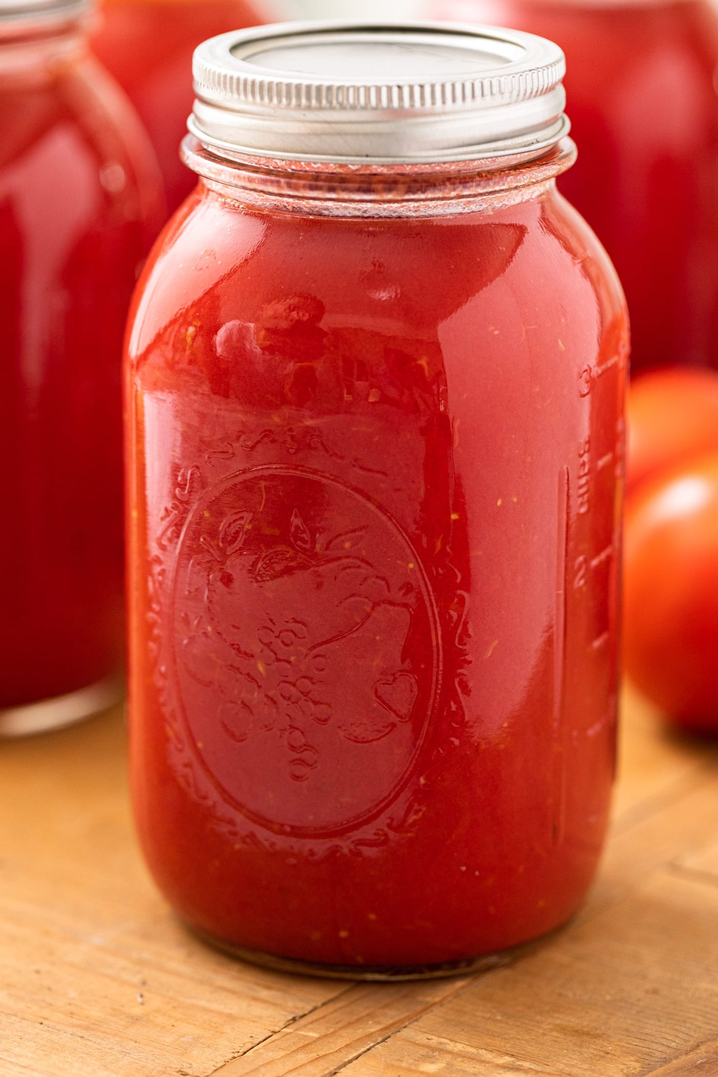 Glass jar filled with tomato juice with lid and ring on top sitting one wooden board