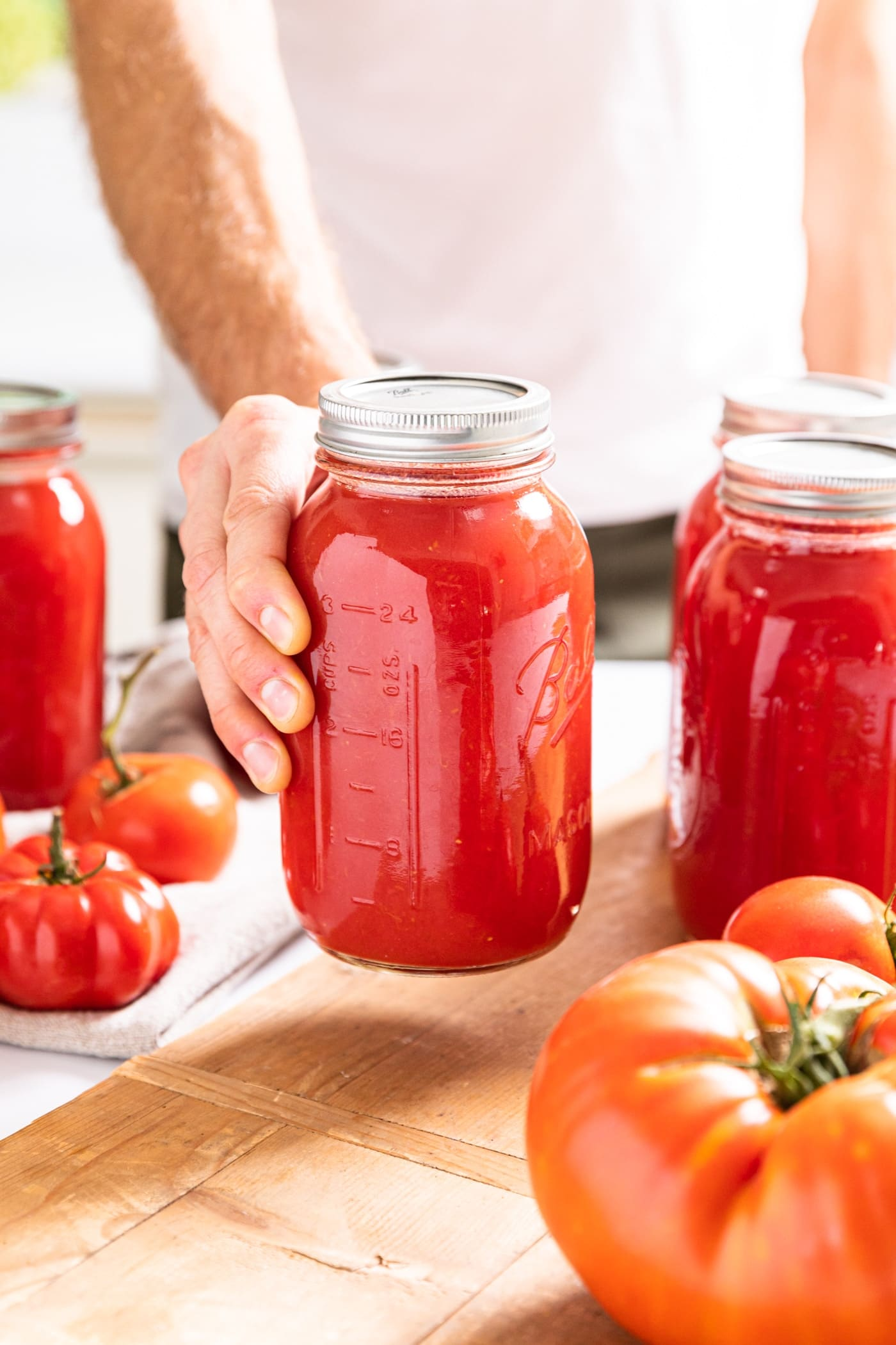Hand holding glass jar filled with red colored tomato juice after being canned with wood board underneath