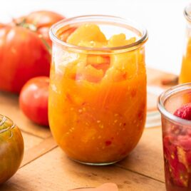 Close up view of large glass container holding yellow and orange colored tomato pieces with extra tomatoes all around all on wood board
