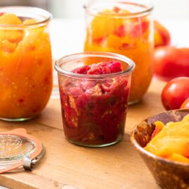 Glass containers filled with red and orange colored sliced tomatoes sitting on wood board