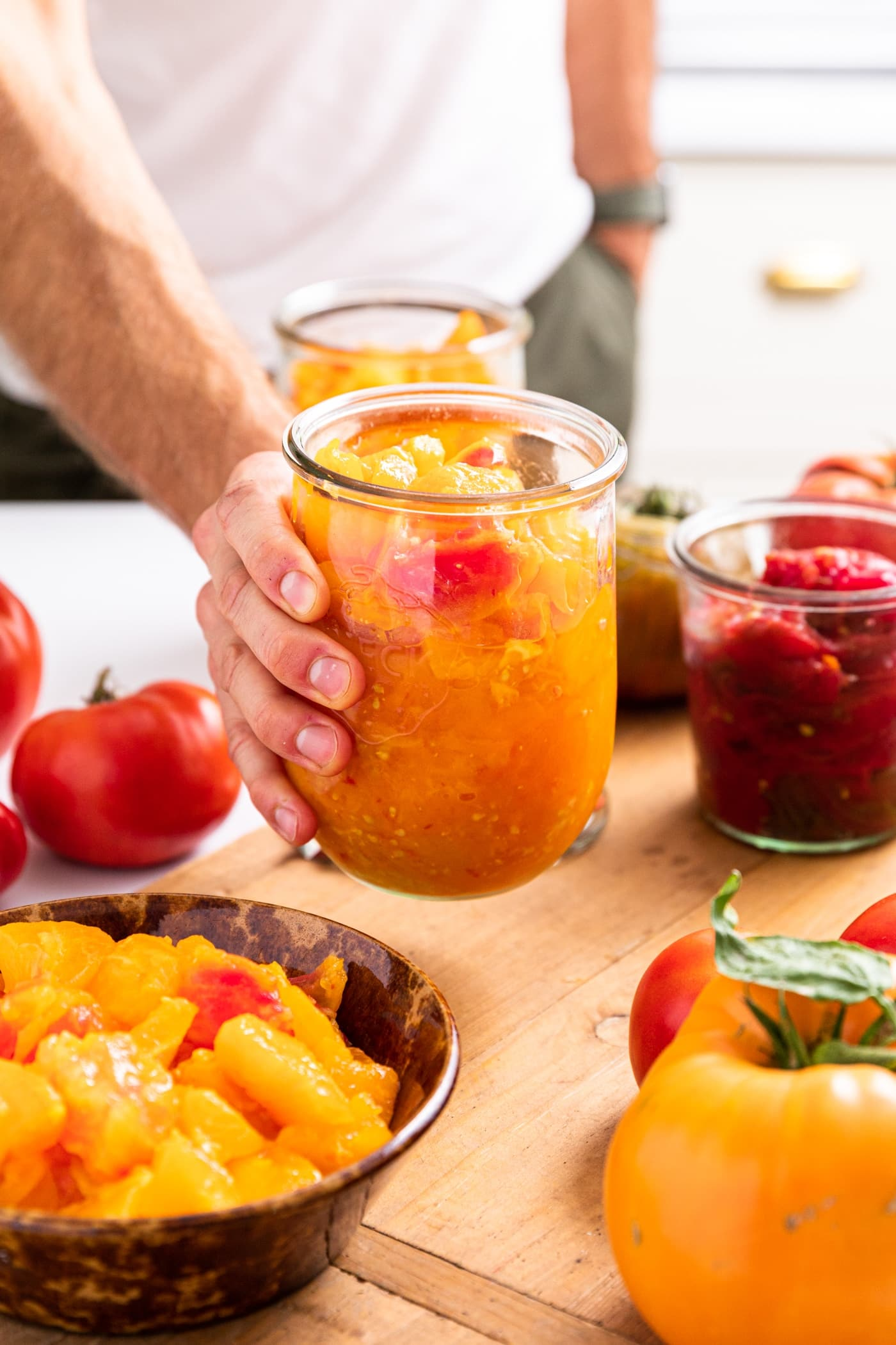 Hand holding glass container filled with red and yellow colored tomatoes all on wood board