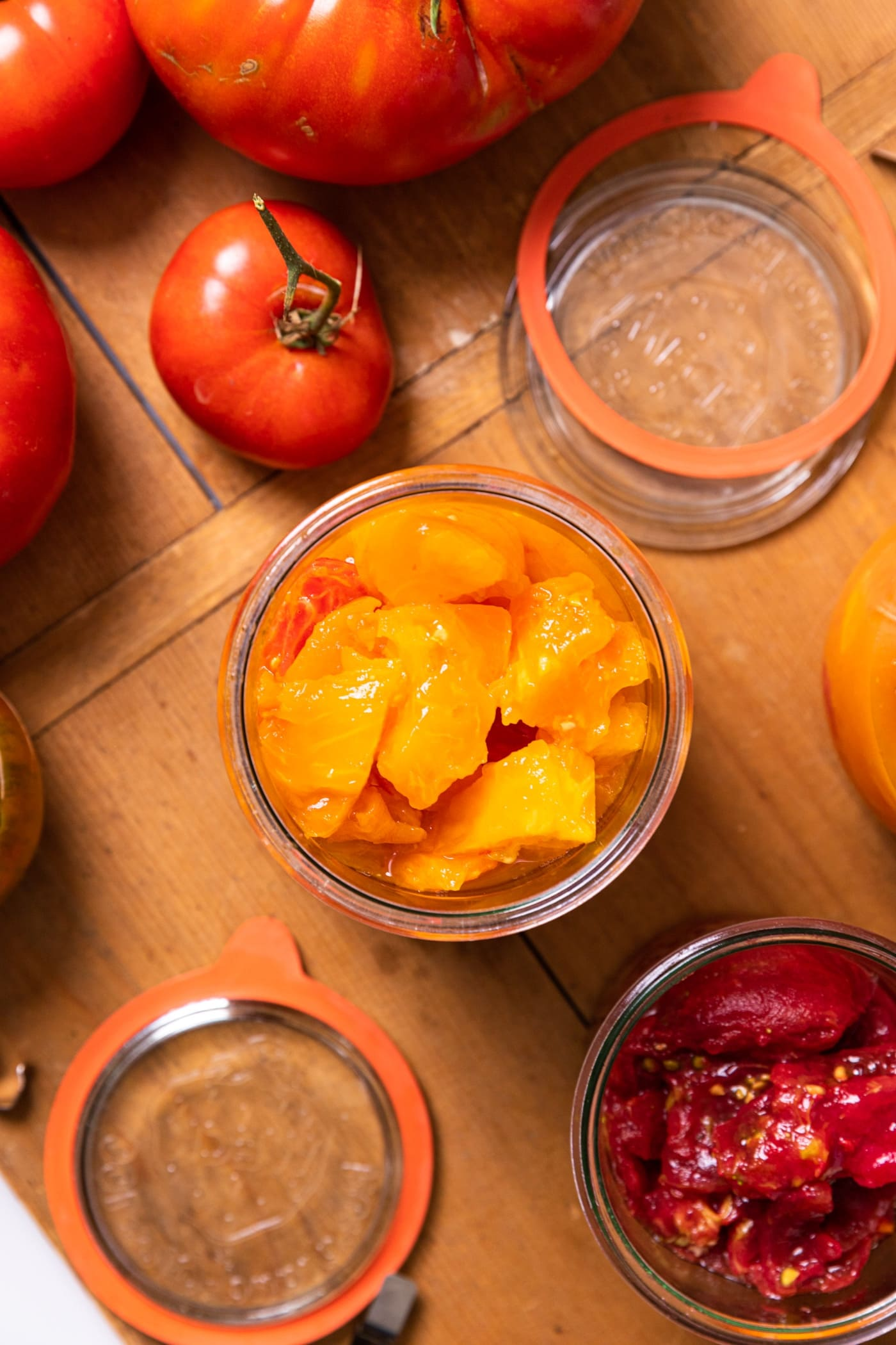 Top down view of yellow and orange colored tomatoes sitting in glass jar with extra tomatoes sitting around on wood board