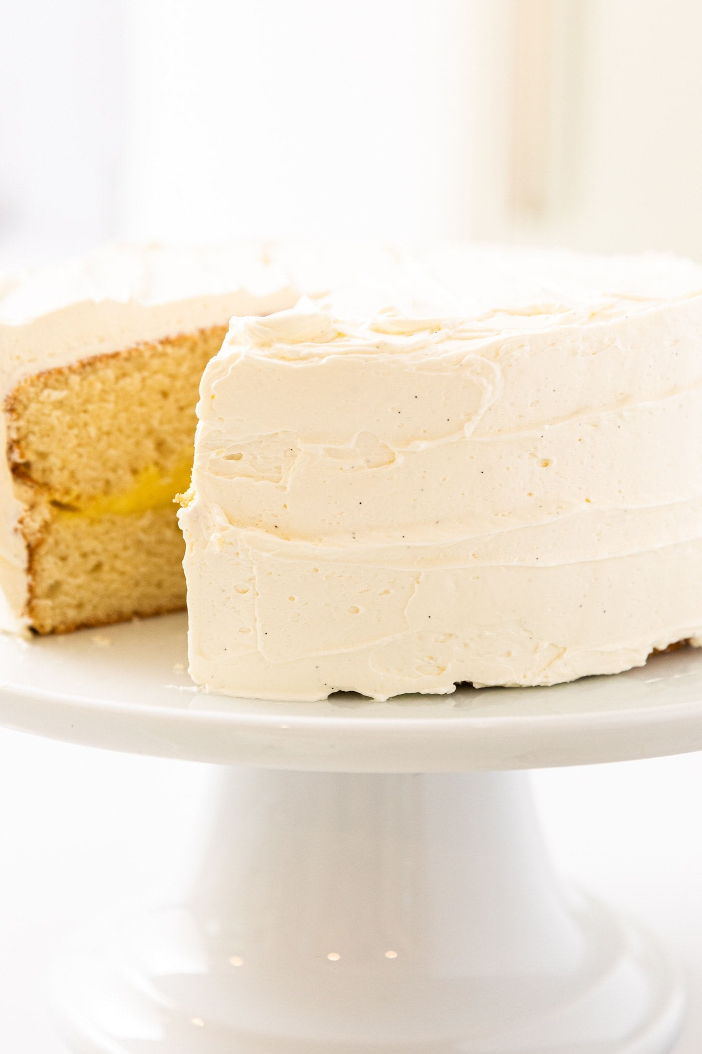 Side view of white frosting on white layer cake sitting on white cake plate