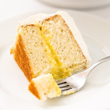 Slice of white layer cake filled with yellow pudding interior with white frosting with fork scooping off piece all on white plate