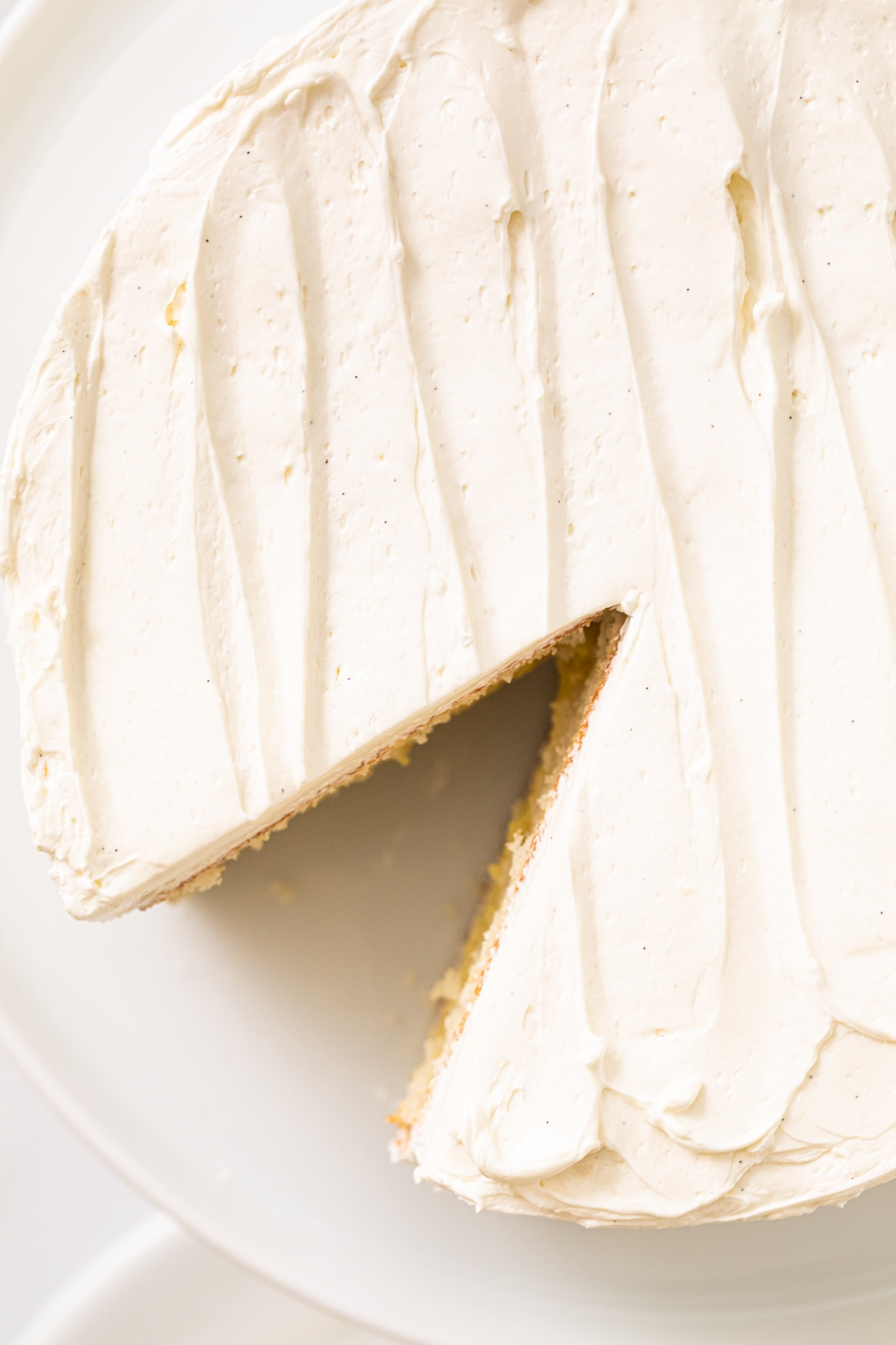 Top down view of white frosted cake with swirled effect on top sitting on white cake plate